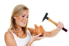 Young woman slaughters her piggy bank Stock Image