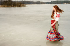 Young woman in Slavic Belarusian national original suit outdoors. Young woman in a Slavic Belarusian national original suit outdoors royalty free stock photo