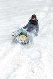 Young woman sledging in the deep snow Stock Photography