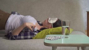 Young woman in a sleep mask tosses and turns in her sleep can not sleep,in the foreground of insomnia pills. Young woman in a sleep mask in a shirt tosses and stock video footage