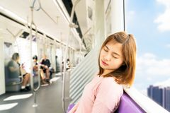 Young woman sleep while taking the sky train. royalty free stock photography