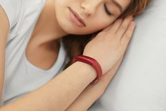 Young woman with sleep tracker resting in bed at home. Closeup stock image