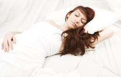 Young woman sleeping. Red hair woman sleeping on a white bed stock image