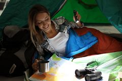 Young woman in sleeping bag with map. And flashlight inside of tent royalty free stock photography