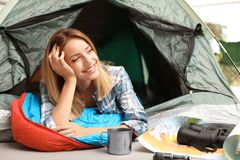 Young woman in sleeping bag. Looking outside of tent royalty free stock photo
