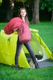 A young woman sleeping bags in a tent while camping. A young woman carries sleeping bags to put in the tent while camping outdoors Royalty Free Stock Image