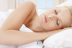 Young woman sleeping in bed. Royalty Free Stock Image
