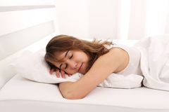 Young Woman sleeping in bed with arm unter pillow. A Young Woman sleeping in bed with arm unter pillow Royalty Free Stock Photography