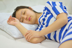 Young woman sleeping on bed in bedroom Stock Photo