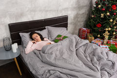 Young woman sleeping in bed and christmas present lying near in Royalty Free Stock Photography