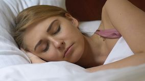 Young woman sleeping in bed in the morning, comfortable orthopedic mattress. Stock footage stock video footage
