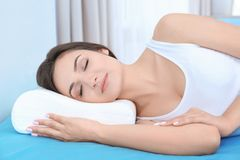 Young woman sleeping on bed with orthopedic pillow. At home. Healthy posture concept royalty free stock photos