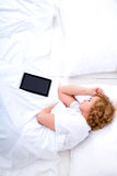 Young woman sleeping in Bed with a Tablet PC Stock Photography