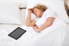 Young woman sleeping in Bed with a Tablet PC Royalty Free Stock Images