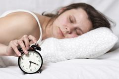 Young woman is sleeping in bed and turns off alarm. Sleep after alarm clock rang. girl wakes up on alarm clock in early morning. Girl in bedroom is lying in Royalty Free Stock Image