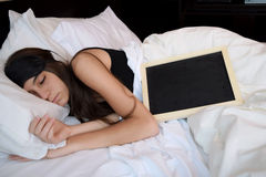 Young woman sleeping with a chalkboard Stock Photos