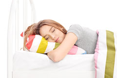 Young woman sleeping in a comfortable bed. Studio shot of a young woman sleeping in a comfortable bed isolated on white background Stock Images