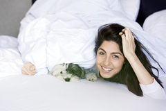 Young woman sleeping with her dog on a bed. Royalty Free Stock Photography