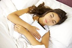 Young woman sleeping hugging tablet in bed Stock Image