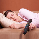 Young Woman Sleeping In Front Of TV Royalty Free Stock Images