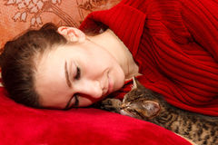 Young woman sleeping with kitten Stock Image