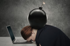 Young woman sleeping on laptop with bomb Stock Photo