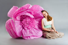 Young woman sleeping near huge flower Stock Photography