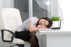 Young woman sleeping in the office. Young woman sleeping on a table in the office Royalty Free Stock Image