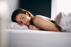 Young woman sleeping peacefully in her bed Stock Images