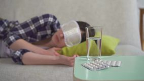 Young woman sleeping on sofa in living room in sleeping mask in foreground insomnia pills. Young woman in a shirt sleeping on sofa in living room in sleeping stock footage
