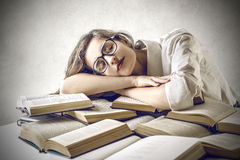 Young woman sleeping on some books. Young beautiful woman felt asleep while studying some books royalty free stock photos