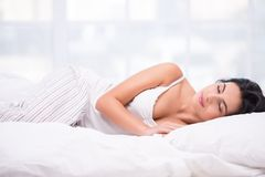 Young woman sleeping in striped pyjamas. Beautiful young dark haired woman sleeping on a white bed wearing striped pyjamas Royalty Free Stock Photos