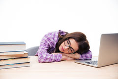 Young woman sleeping on the table. Young woman in glasses sleeping on the table over white background Royalty Free Stock Photo