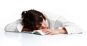 Young woman sleeping tired of learning. Young woman sleeping on a table tired of reading, on white background royalty free stock photos
