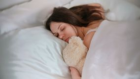 Young woman sleeping with a toy bear.