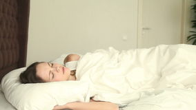 Young woman sleeping on uncomfortable bed. Young beautiful female having problems with her sleep, moving on bed, unable to fall asleep, lying on uncomfortable stock video footage