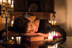 Young woman sleeping under candlelights after reading book Stock Images