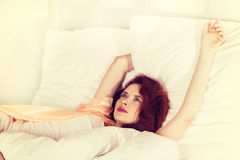 Young woman sleeping on the white bed-clothes in bed at home Royalty Free Stock Photography