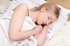 Young woman sleeps on bed in bedroom at home Stock Photos