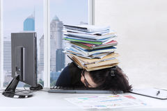 Young woman sleeps on keyboard with documents Stock Photography