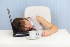 Young woman sleeps on laptop keyboard on workplace Stock Photo