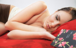 Young woman sleeps on red Stock Image