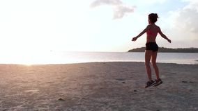 A young woman jogging at the beach on sunset. aerial drone shot, slow motion. A young woman with a slender figure jogging at the beach at sunset. She makes a stock video footage