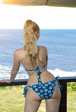 Young woman with a slender waist and wide hips in a swimsuit  stand on a terrace and looks at the sea Stock Photos