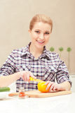 Young woman slices yellow pepper Royalty Free Stock Photo
