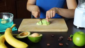 Young Woman Slicing Avocado on a Cutting Board. Close Up of Young Woman Slicing Avocado on a Cutting Board. Process of Making a Homemade Smoothie. Healthy Eating stock video footage