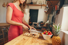 Young woman slicing a loaf of bread in kitchen Royalty Free Stock Photo