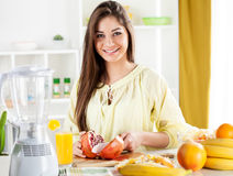 Young woman slicing pomegranate Stock Images