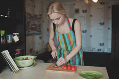 Young woman slicing tomatoes. In home kitchen Royalty Free Stock Photo