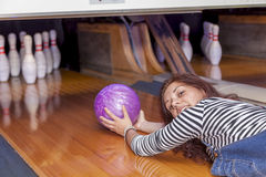 Young woman sliding down a bowling alley. Funny young woman sliding down a bowling alley Royalty Free Stock Photo